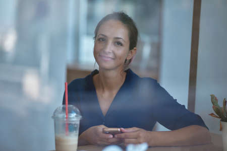 Smiling girl with smartphone. Cup of drink on table. Enjoy life and little moments. Coffee break and leisure time idea