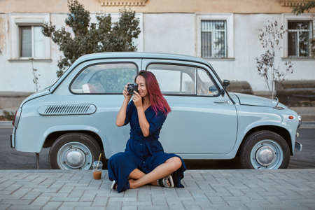 Lovely young woman holding photocamera. Lady sitting on street near car. New emotion, new place and travel time concept 写真素材