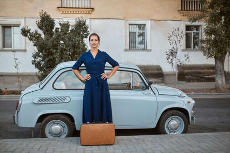 Woman in blue dress and suitcase on ground. Old vintage car on background. Travel time and new places idea, copy space