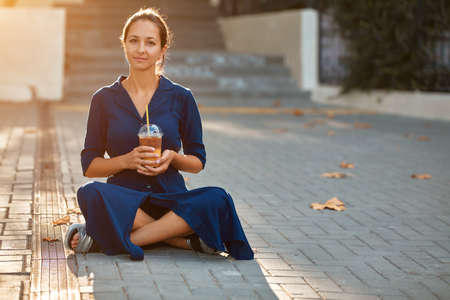 Attractive woman in blue dress sitting on ground. Spare time on nature. Take break and coffee time concept, copy space