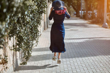 Woman walking on hop on road. Sunlight fall on asphalt. Happy lady in blue dress. Street style and leisure time idea