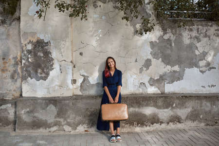 Smiling pretty woman with suitcase. Lady posing on old wall background. Travel time, new emotion and new place concept 写真素材