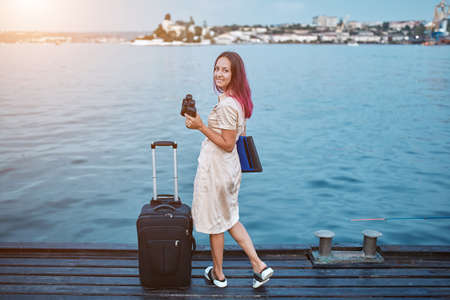 Pretty woman with binoculars standing on pier. Suitcase and laptop for trip. Travel time, adventure and new ground idea