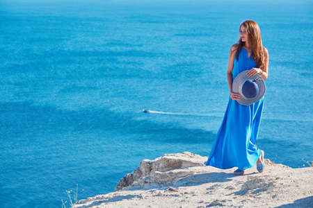 Travel and relax time idea, copy space. Young lady feeling good enjoying holiday near sea. Panoramic view from mountain.