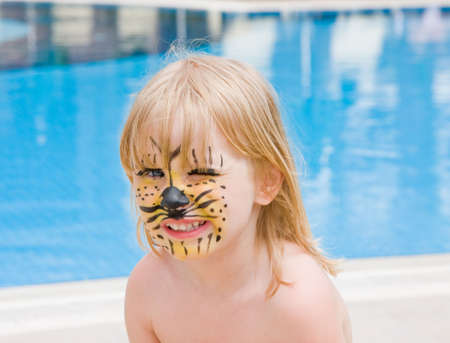 Girl with paint on his face in the pool photo
