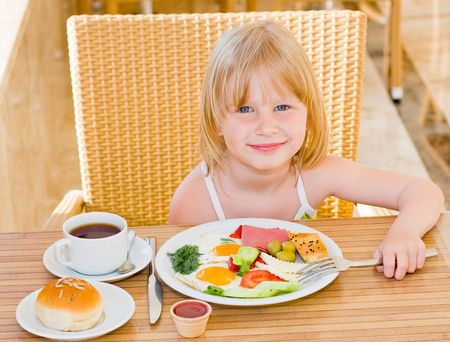 Young girl eating in restaurant Stock Photo - 5110417