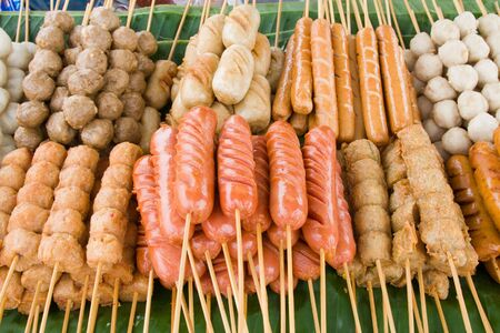 Meatballs on sticks, dipped in sweet chili sauce at a market in Thailand  photo