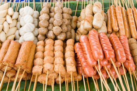 Meatballs on sticks, dipped in sweet chili sauce at a market in Thailand