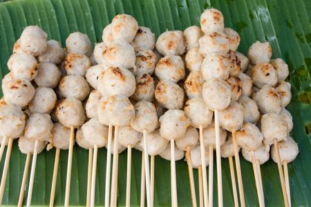 Meatballs on sticks at a market in Thailand  photo