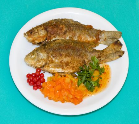 Fried fish in plate on a green background