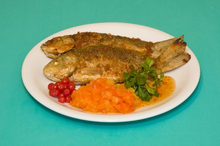 Fried fish in plate on a green background photo
