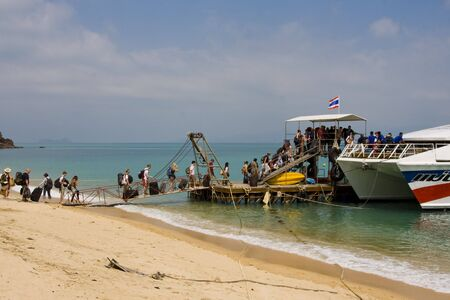 SAMUI - JANUARY 21: Tourists are going to land from a boat floating on the island Phangan on January 21, 2010 in Samui, Thailand. On Phangan Island takes place every month the FULL moon party.