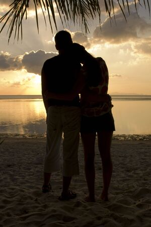 Silhouette of romantic couple on tropical beach at sunset photo