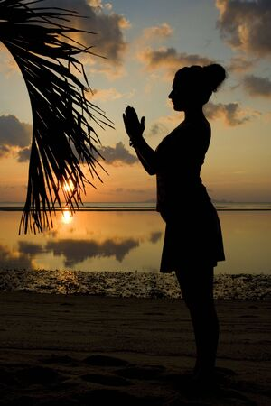 Woman silhouette with her hands raised in the sunset photo