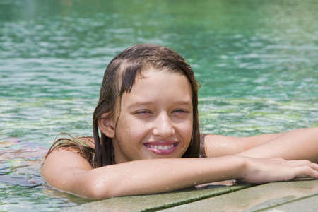 Girl portrait relaxing in swimming pool at exotic surrounding, Asia. photo