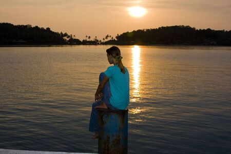 Girl siting on a sunset photo