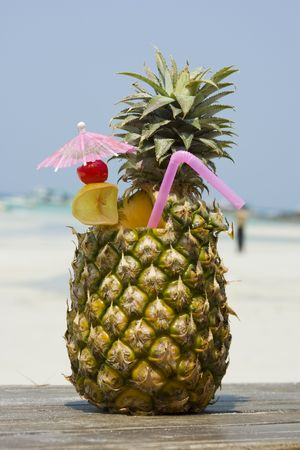 Tropical pineapple cocktail drink at the beach overlooking the ocean photo