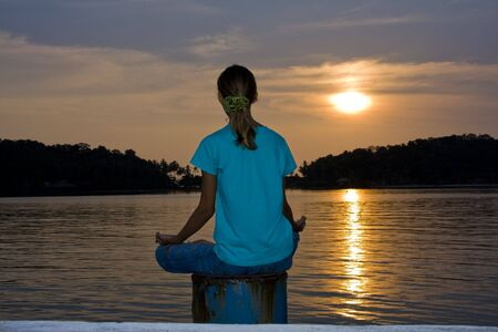 Girl doing yoga on a sunset photo