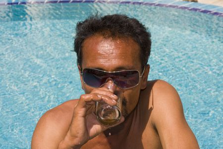 Thai man drinking beer in the pool  photo