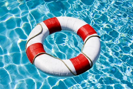 pool symbol: Life ring floating on top of sunny blue water Stock Photo