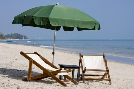 Wooden beach chairs under umbrella. photo