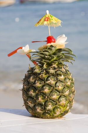 Tropical pineapple cocktail drink at the beach overlooking the ocean Stock Photo