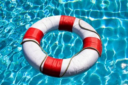 人生はリングを日当たりの良い青い水面に浮かぶ 写真素材