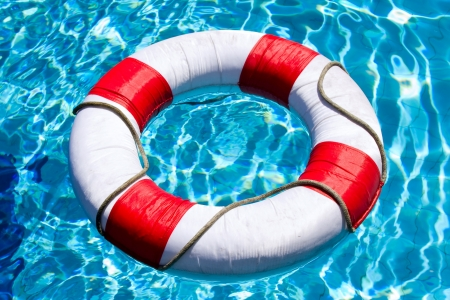 drowning: Life ring floating on top of sunny blue water Stock Photo