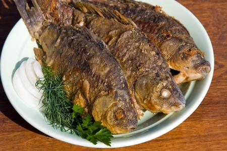 Fried fish crucian in plate on wooden table photo