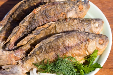 Fried fish carp in plate on wooden table photo
