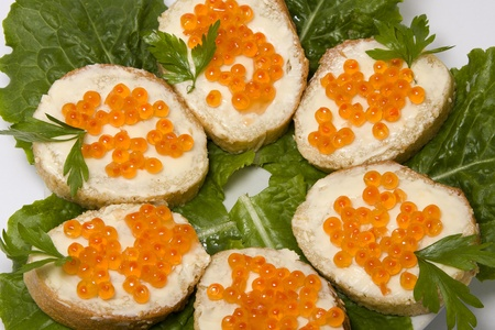Red caviar sandwiches on white plate . photo