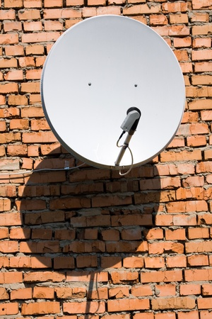 Satellite antenna on the wall of a brick house photo