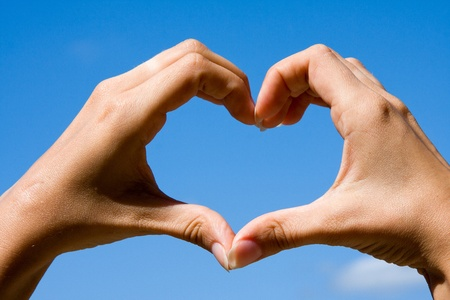 express feelings: Heart shaped from hands against clear blue sky