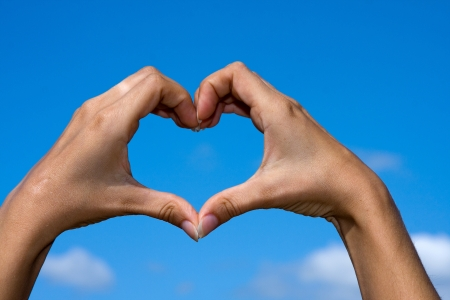 Heart shaped from hands against clear blue sky