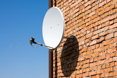 dish disk: Satellite antenna on the wall of a brick house