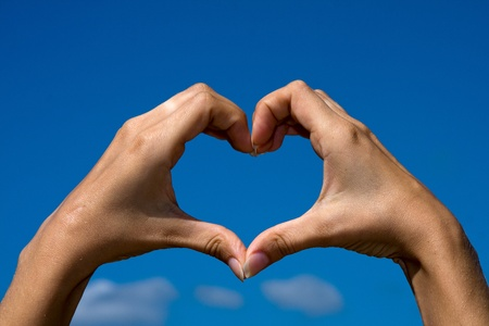 Heart shaped from hands against clear blue sky photo