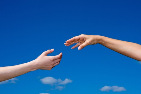 the faithful: Hand reaching out from the blue sky Stock Photo