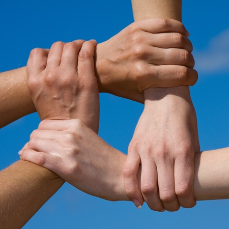 Couple hands connecting to a chain with blue sky photo