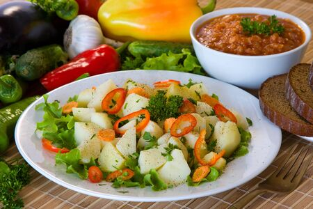 Boiled potatoes with vegetables on white plate photo