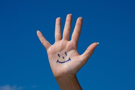 glädje: Human palm med leende på blå himmel bakgrund