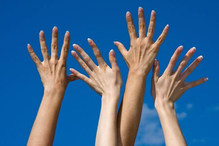 Raised hands on blue sky background with copy space photo