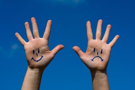 feeling positive: Palma en el cielo con un patr�n de la sonrisa y la tristeza Foto de archivo