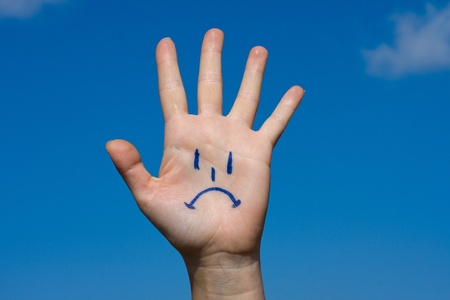 Human palm with sorrow on blue sky background