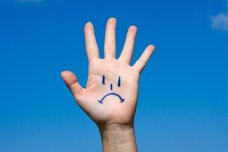 sadness: Human palm with sorrow pattern on blue sky background
