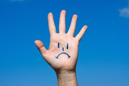 cabizbajo: Palma humana con motivo de tristeza sobre fondo de cielo azul