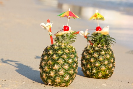 Two tropical pineapple cocktails on the beach photo