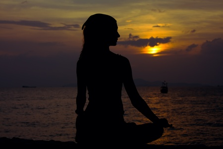 Healthy woman doing yoga outdoor, sunset over sea 스톡 콘텐츠