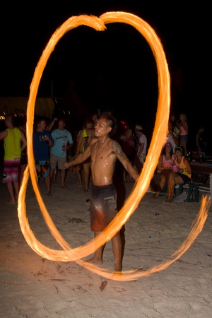 PHANGAN - JANUARY 08 : There are about 10,000 people every month at this Phangan beach Full moon party, on January 08, 2012 in Koh Phangan , Thailand . Fire dancer on a beach - blur