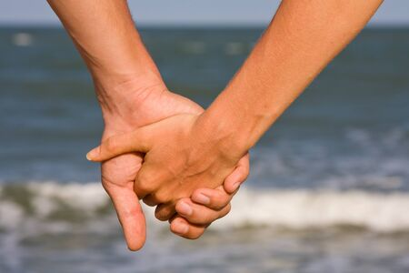 Couple of hands against the sea view photo