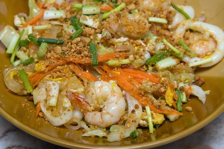 Pad thai with seafood. Thai noodle with seafood on white plate photo